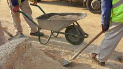 Uhd construction site, workers load sand manualy for concrite preparation. so Stock Footage