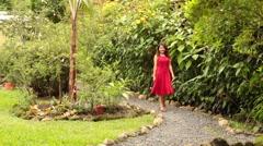 Beautiful Trim Brunette in Red Dress Walking Along Gravel Garden Path - stock footage