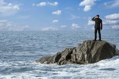 Observing man on rocks in the sea, montage Stock Photos