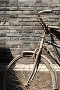 Old bike leaning against brick wall in a Chinese hutong - stock photo