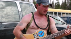A man playing guitar rainbow family gathering in heber utah 2014 Stock Footage