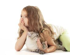 Little girl hugged her cat and dreaming. - stock photo