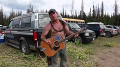 Man playing guitar rainbow family gathering in heber utah 2014 Stock Footage