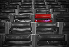 Single red chair in amongst rows of monochrome chairs Stock Photos