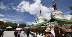 4k tibet people turn spinning buddhist prayer wheels,Potala & white stupa. Stock Footage