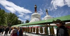 4k tibet people turn spinning buddhist prayer wheels,Potala & white stupa. Stock Footage
