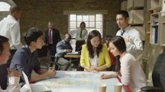 4K Asian business team in strategy meeting, looking at a map of the world - stock footage