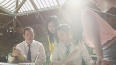 Asian business team in strategy meeting, looking at a map of the world - stock footage