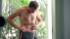 Happy slim man measuring his waist in the bathroom HD Stock Footage