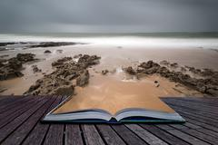 Long exposure landscape beach scene with moody sky conceptual book image Stock Photos