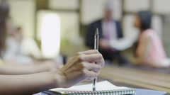 Close up hand of businesswoman tapping her pen in a boardroom meeting - stock footage