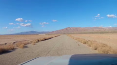 Driving On Old Road In Barren Desert- Viewpoint Shot Stock Footage