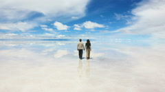 Man and woman walking at the lake Salar de Uyuni Stock Footage