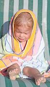 Baby in colored towel crying outdoor - stock photo