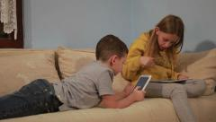 Two kids boy and girl playing games on tablets and having a funny reaction. Stock Footage