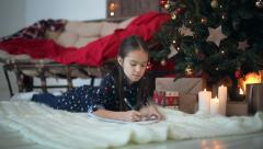 Child girl writes a letter to Santa Claus. Dolly shot Stock Footage