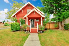 small coutnryside house exterior in bright red color with white trim - stock photo