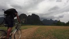 Tourist Cycling Through the Contryside in Vang Vieng, Vientiane Province, Laos Stock Footage