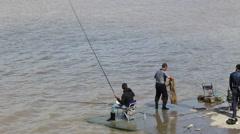 People fishing at riverside Stock Footage