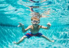 Young boy diving underwater in swimming pool Stock Photos