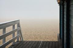 beach in fog with balustrade and stairs - stock photo