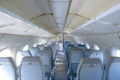 Interior of an airplane with many seats Stock Photos