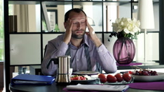 Young businessman having headache during breakfast at home HD Stock Footage