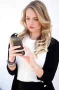 Pretty businesswoman with smart phone sending text sms Stock Photos