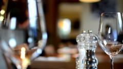 Restaurant - empty wine glasses with salt cellar - people in background Stock Footage