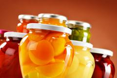 Stock Photo of jars with fruity compotes and jams. preserved fruits.