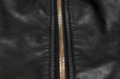 close up of zip on black leather material - stock photo