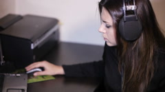 Girl with headphones at table Stock Footage