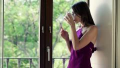 Young, pensive woman drinking coffee and looking by the window HD - stock footage