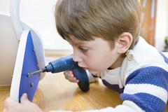Little boy using diy tool at home Stock Photos