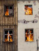 Fire bursts through two windows on the side of a house Stock Photos