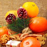 christmas tangerines with sweet delights, walnuts, pinecone and brittle candi - stock photo