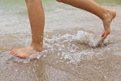 feet of boy running along the beach - stock photo