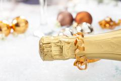 Stock Photo of champagne bottle and christmas balls on icy background