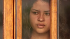 Beautiful Latina WomanStands at Window With Contemplative Look Stock Footage
