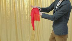 Stock Video Footage of Magician shows tricks with red cloth