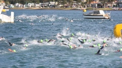 Competitors depart from start of swimming leg of triathlon Stock Footage