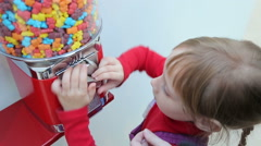 Girl gets candy from machine sale of sweets - stock footage