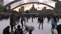 People ice skating at Toronto city hall rink on cold winter day Stock Footage