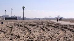 Running jogging people sand beach ferris wheel Los Angeles California Stock Footage
