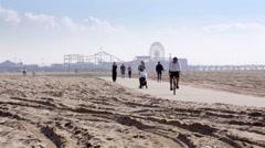 People jogging running bicycles sand beach ferris wheel Los Angeles California Stock Footage