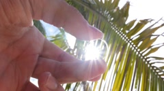 Wedding Rings in Hand against Palms and Bright Sun. Slow Motion. Stock Footage