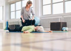 Physical therapist assisting senior woman with leg exercise Stock Photos