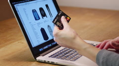 Shopping for a dress online with credit card in hand - stock footage