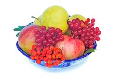 Apples, pears, berries and rowan in a vase on a white background. Stock Photos