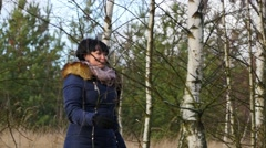 Pretty warmly clothed woman walking in birch forest in cold winter time Stock Footage